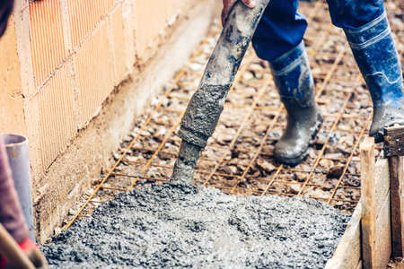 vibration machine: close up of industrial worker pouring cement or concrete with automatic pump tube