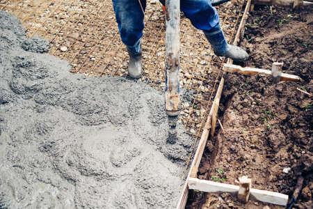 concrete pump: top close up view of worker handling a massive cement or concrete pump on construction site