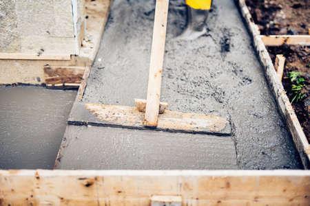 cemento: edificio Mason y nivelación de una primera capa de suelo de hormigón fresco en las escaleras de las casas y las aceras, emplazamiento de la obra