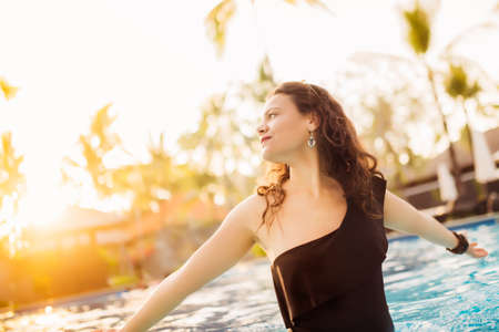 perfectly: Elegant sexy woman with perfectly tanned body posing in swimming pool at luxurious hotel Stock Photo