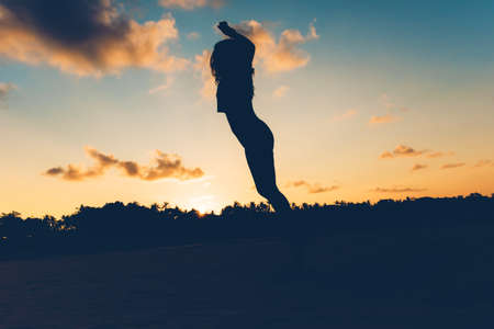 stress free: silhouette of Beautiful brunette jumping on beach at sunset, carefree and stress free woman on island. Stock Photo