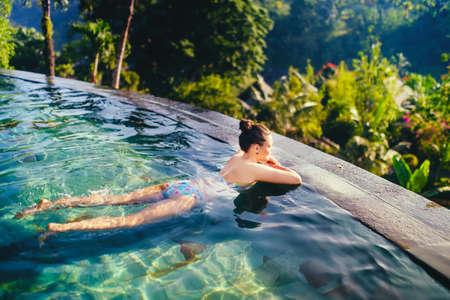 Jonge mooie vrouw in openlucht zwembad. Concept van de vakantie met vrouw zonnen in oneindig zwembad