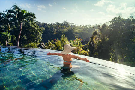 sexy Frau, die Sonne im Unendlichen Sommer Schwimmbad in Luxus-Resort genießen