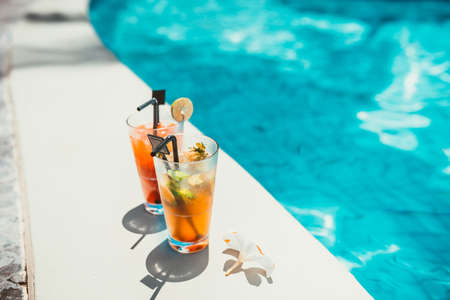 close-up of two alcoholic drinks, ice and gin and tonic lemonade and mojito with lime served cold at pool bar Stock Photo