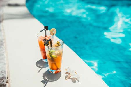 Close-up van twee alcoholische dranken, ijs en gin en tonic limonade en mojito met limoen geserveerd koud bij pool bar