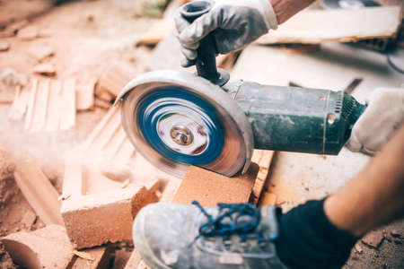 putty: worker using grinder on construction site for cutting bricks, debris. Tools and bricks on new building site