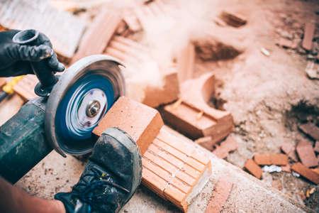 Industrial worker cutting through bricks. Professional brickmason using grinder at building houses
