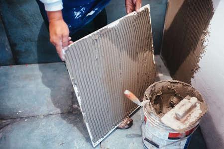 Industrial Worker Installing Bathroom Ceramic Floor Tiles Adding