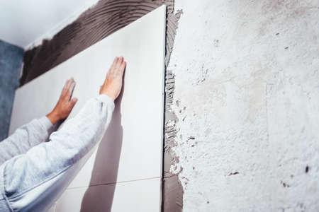 Industrial Worker Handyman Installing Big Ceramic Tiles On Bathroom