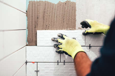 industrial construction worker installing small ceramic tiles on bathroom walls and applying mortar with trowel