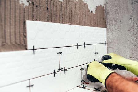 Renovatie in uitvoering. Industriële werker installeren van keramische tegels Stockfoto