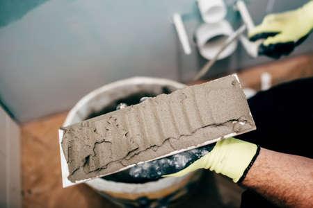 obrero trabajando: trabajador de la construcción la aplicación de mortero sobre las baldosas cerámicas y trabajando en la reconstrucción de un cuarto de baño