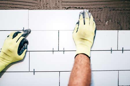 ceramic tiles: industrial worker hands installing ceramic tiles on interior walls, handyman using plastic distancer for adjusting tiles. Construction details