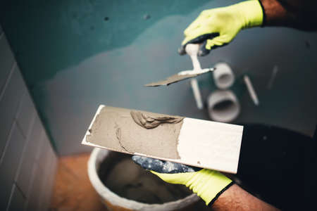 tile adhesive: industrial close up detail of worker adding cement adhesive on small ceramic tiles Stock Photo