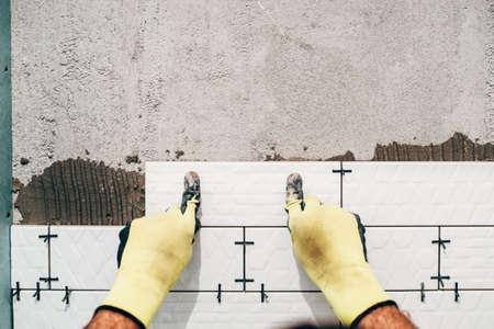 bathroom tiles: industrial worker, handyman installing small ceramic tiles on bathroom walls