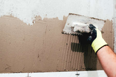 Cement Voegen Badkamer : Industriële werknemer met keramische tegels en het aanbrengen van
