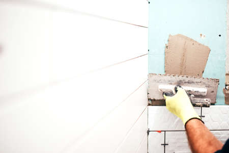 masonry: renovation in progress, construction details, close up of worker hands using trowel and adding adhesive Stock Photo