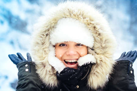 cold season: Outdoor portrait of happy, smiling woman, enjoying snow and winter days during cold season. Stylish portrait of beautiful woman