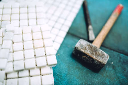 Close up details of construction tools, bathroom and kitchen renovation - pieces of mosaic ceramic tiles and rubber hammer