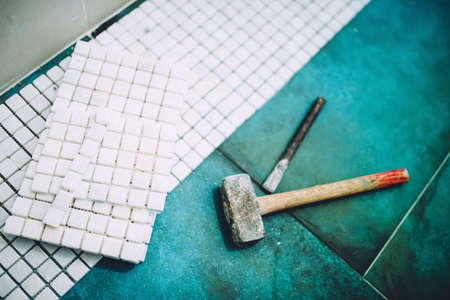 Industrial details of home construction - Hammer and mosaic, white marble stone ceramic tiles Stock Photo