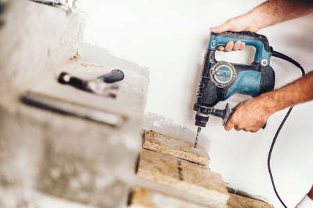 Precise wood worker using professional drill press for making holes in wood boards and concrete Stock Photo
