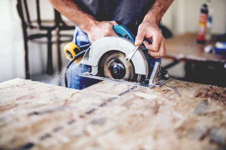 Carpenter przy użyciu piły tarczowej do cięcia desek. Szczegóły konstrukcyjne męskiej pracownika lub przystojny mężczyzna z elektronarzędziami