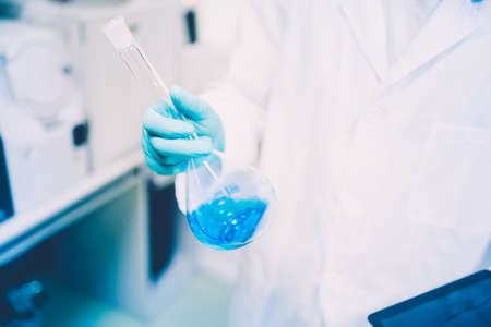 Male scientist conducting experiments in chemical laboratory with liquid substances, testing samples  Stock Photo