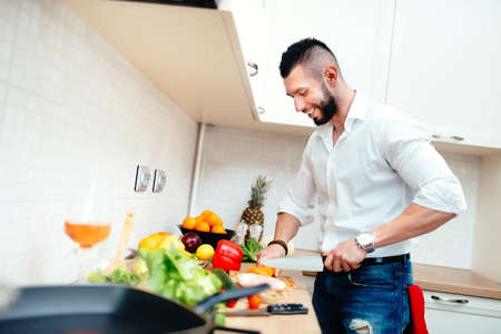 Happy smiling man cutting vegetables for salad or soup. Young professional well dressed cook preparing food in new kitchen
