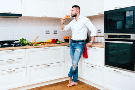 tomando vino: handsome man cooking and drinking a glass of wine.  Foto de archivo