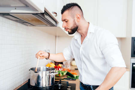 handsome man cooking and boiling pasta. healthy lifestyle details Imagens