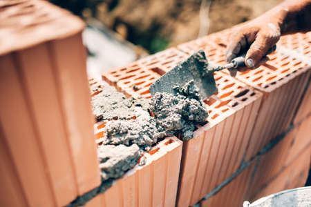 Industrial worker using trowel and tools for building exterior walls with bricks and mortar Stock Photo