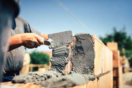 mortero: Albañil trabajador de la construcción de la instalación de ladrillo de mampostería en la pared exterior con espátula cuchillo de masilla