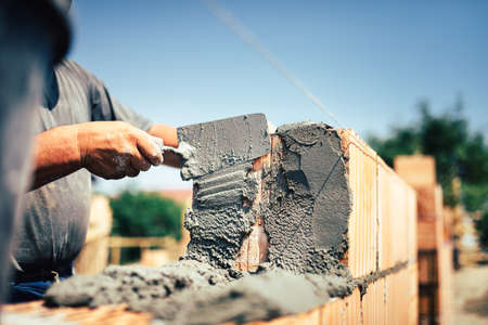 construct site: Bricklayer construction worker installing brick masonry on exterior wall with trowel putty knife