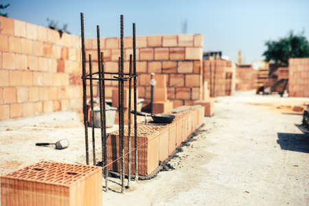 industrial industry: industrial construction site, placing bricks on cement while building exterior walls, industry details Stock Photo