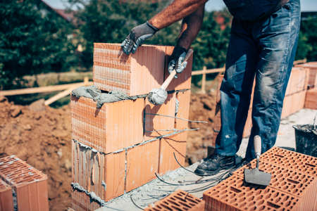 industrial industry: industrial construction worker, professional bricklayer worker placing bricks on cement while building exterior walls, industry details Stock Photo