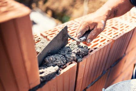 Détails industriels - Ouvrier maçon en bâtiment construisant des murs avec un couteau pour briques, mortier et mastic Banque d'images - 71990919