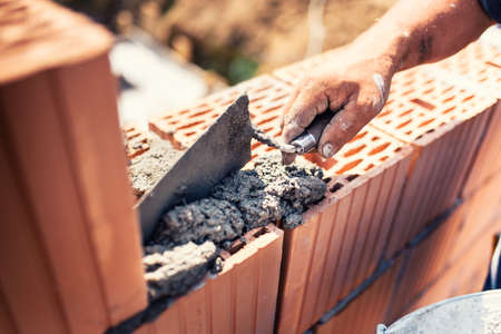 industrial details - Construction bricklayer worker building walls with bricks, mortar and putty knife  Reklamní fotografie