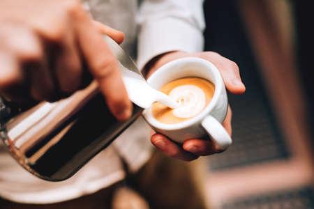 capuchino: Profesional barista verter latte de espuma sobre el café, espresso y la creación de un cappuccino perfecto