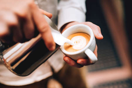 Professional barista pouring latte foame over coffee, espresso and creating a perfect cappuccino Standard-Bild