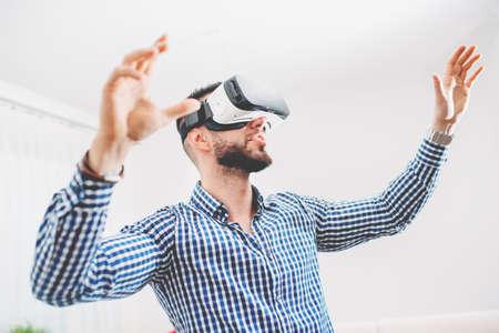 jugando videojuegos: Guapo, hombre con barba que llevaba gafas de realidad virtual en estudio moderno diseño interior de coworking. Smartphone establece con las gafas de realidad virtual y el sonido 3d