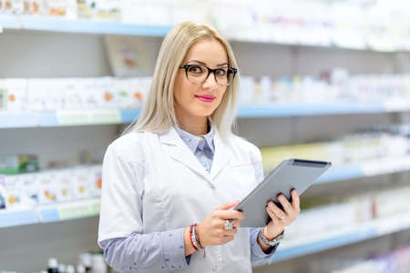health professional: Cute blonde doctor in white uniform using tablet and technology in pharmaceutical or medical field