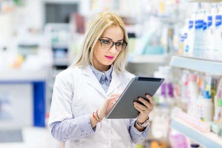 Apotheekdetails - blonde arts in witte eenvormige gebruikende tablet en technologie op farmaceutisch of medisch gebied