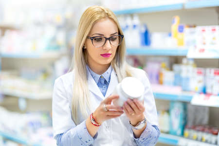 Professional doctor, medical nurse and pharmacist reading the drug label in pharmacy Stock Photo