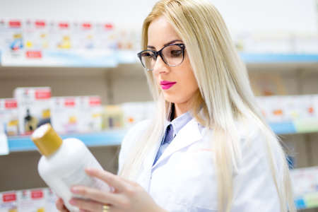 a lady doctor: Young blonde pharmacist looking at pills and creams in store. Female medical assistant reading on labels