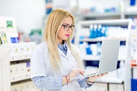 health professional: pharmacist chemist woman standing in pharmacy drugstore and using laptop for network social media