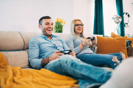 jugando videojuegos: Joven pareja divertirse y riendo mientras se juega juegos de video en la sala de estar moderna