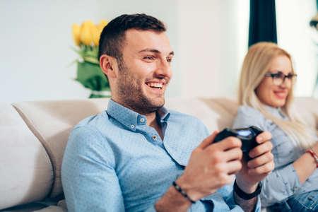jugando videojuegos: Atractivo hombre jugando videojuegos con su esposa o novia en la consola general. Foto de archivo