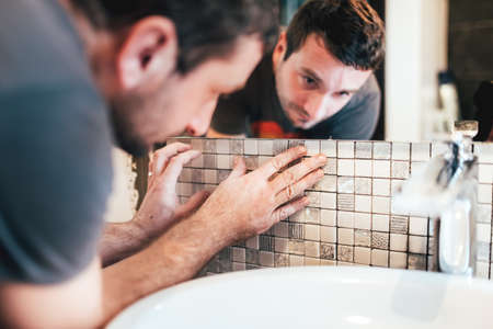 Young male worker installing ceramic mosaic tiles on bathroom walls