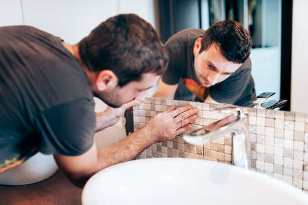 Industry renovation details. Construction details with handyman or worker adding mosaic ceramic tiles on bathroom walls
