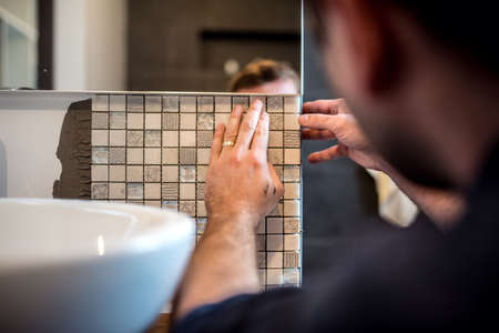 욕실 벽에 모자이크 타일을 적용하는 산업 작업자